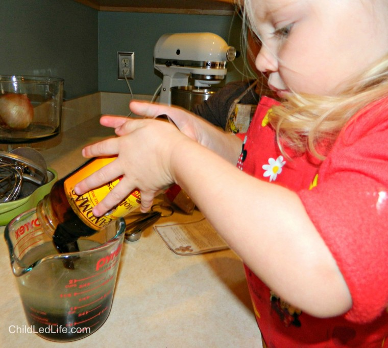 Pouring is a great practical life skill to use in the kitchen. Adding molasses to our #gingerbread cookie recipe on ChildLedLife.com