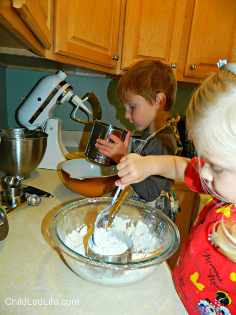 Kids love to help in the kitchen. Sifting and scooping was the highlight while making #gingerbread cookies at ChildLedLife.com