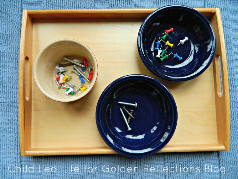 Sorting screws and pushpins is a great sensory work for your child. Find more on Golden Reflections Blog